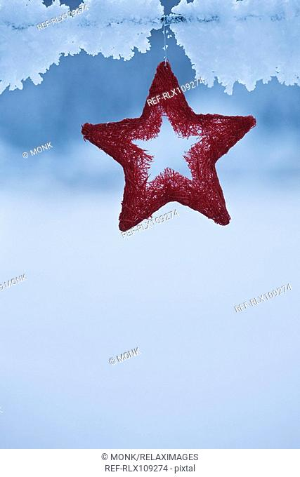 Red star Christmas decoration hanging in snow, close-up