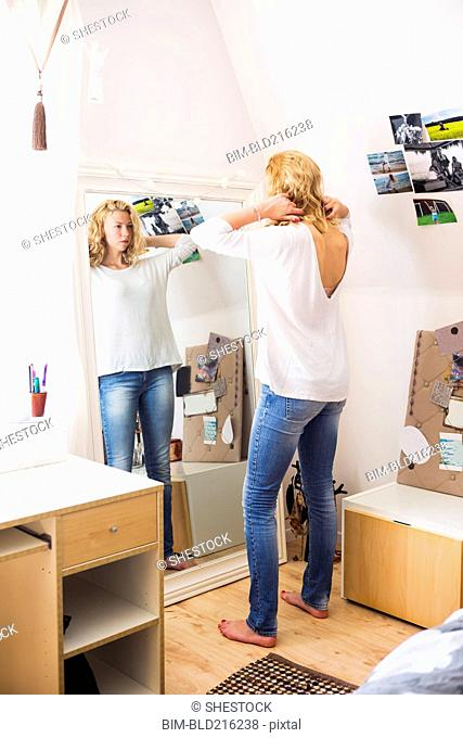Woman styling her hair in mirror