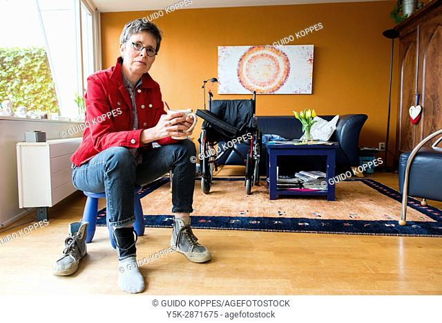 Tilburg, Netherlands. Living room portrait of a mature adult woman suffering from Multiple Sclerosis sitting besides her unused wheelchair