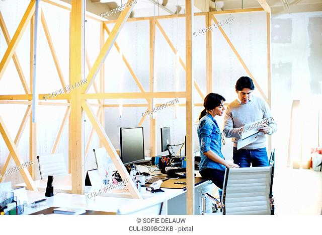 Architects having discussion at workstations