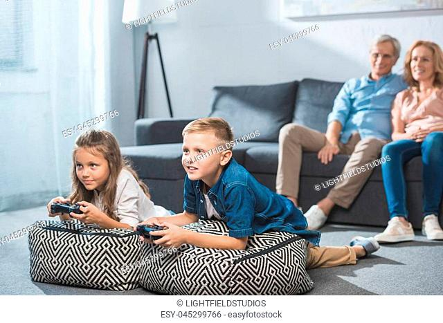 children playing video game with joysticks white grandparents sitting behind