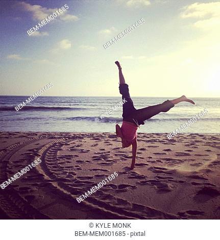 Caucasian woman doing handstand on beach