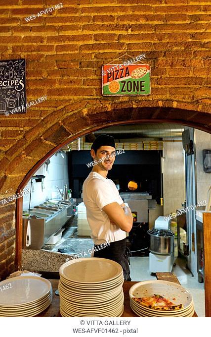 Portrait of confident pizza baker standing in kitchen
