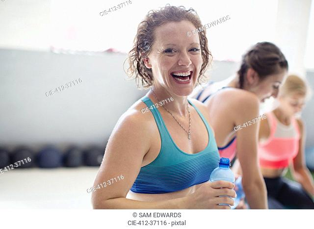 Portrait smiling, laughing woman drinking water and resting post workout at gym