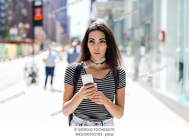 USA, New York City, young woman holding cell phone in Manhattan