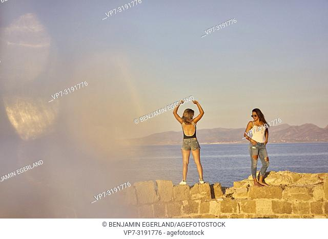two friends on ancient ruins at seaside, hanging out. In Chersonissos, Crete, Greece