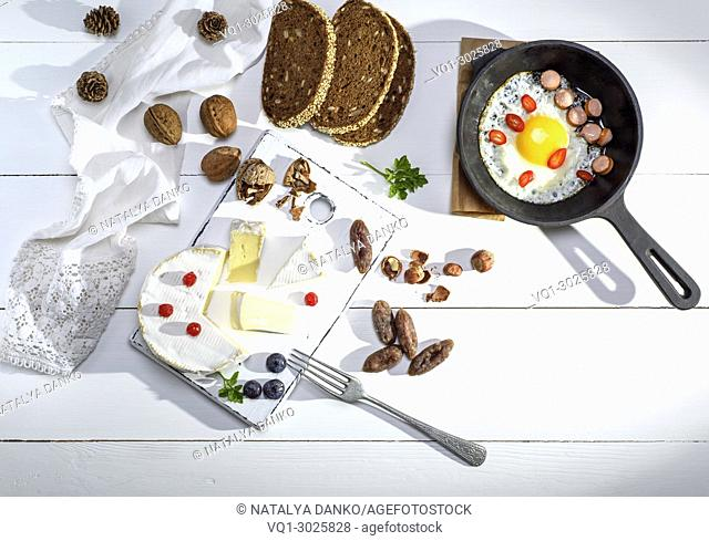 round camembert cheese, pieces of smoked sausage and a round black cast-iron frying pan with a fried chicken egg on a white wooden table, top view