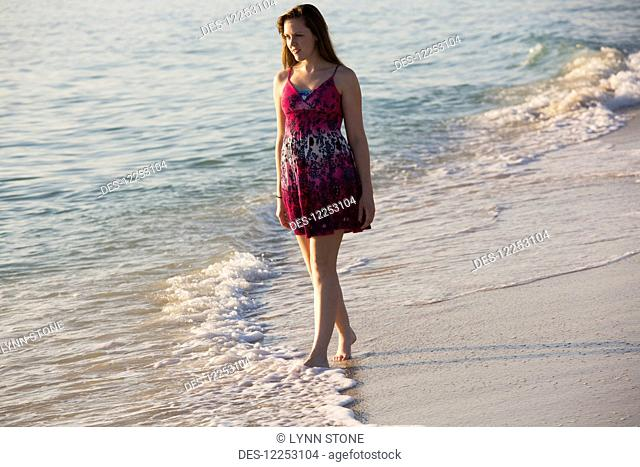 A young woman walks on the beach at the water's edge; Nokomis, Florida, United States of America