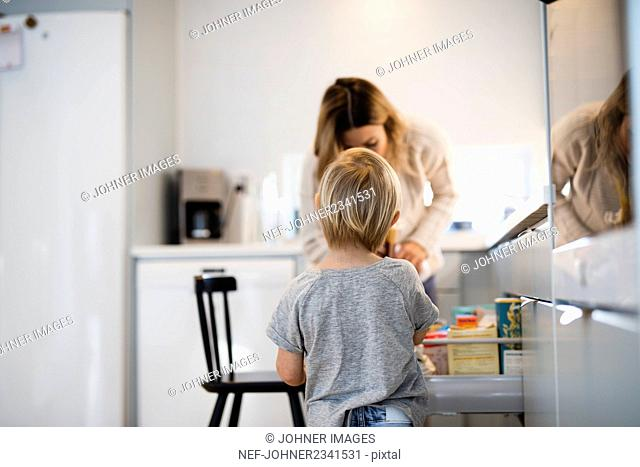 Boy with mother in kitchen