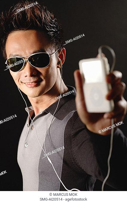 Man in sunglasses, holding MP3 player