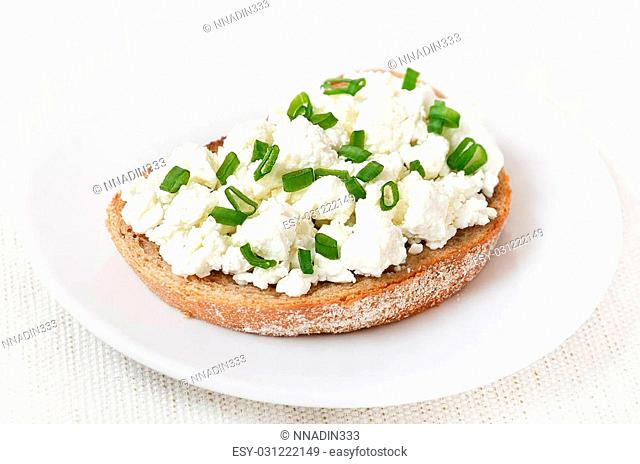 Appetizer with curd cheese and green onion on white plate, close up