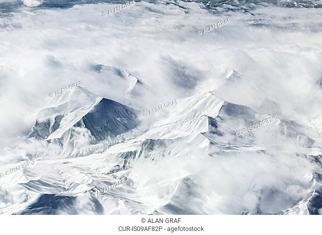 Aerial view of cloud and snow covered mountains, Western China, East Asia