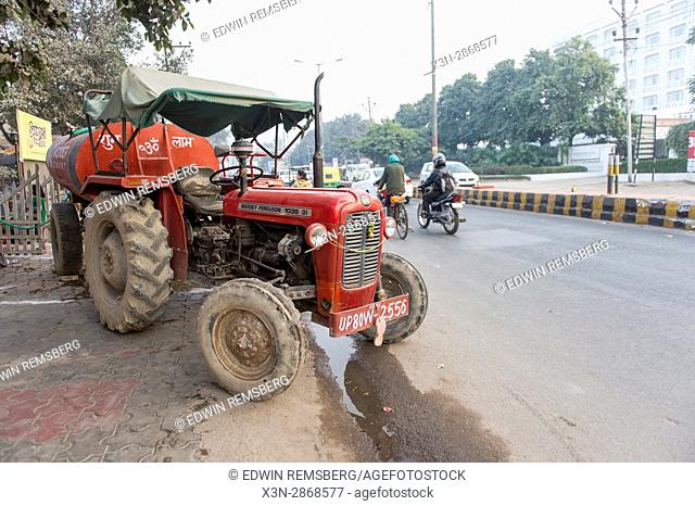 A large tractor is parked on a busy street in downtown Agra, India