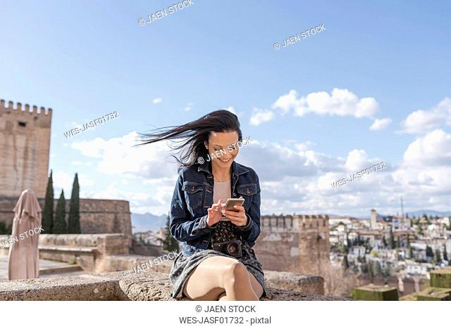 Spain, Granada, smiling young woman using cell phone at the Alhambra