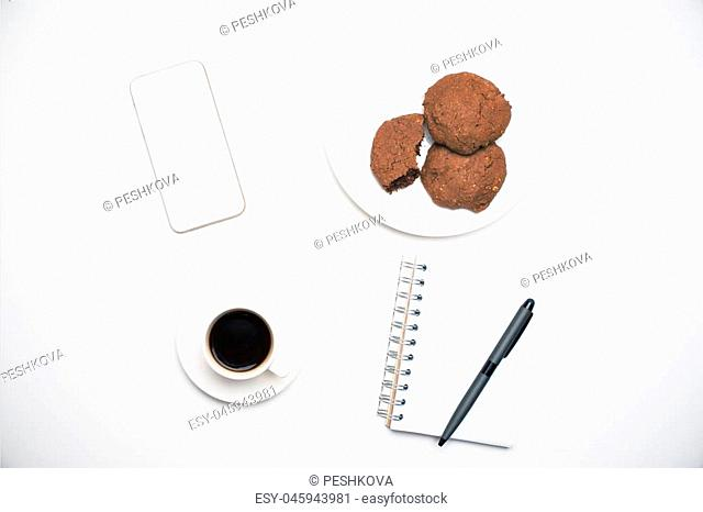 Top view of office desktop with blank white cellular phone, notepad and pen, coffee cup and cookies on plate. Mock up