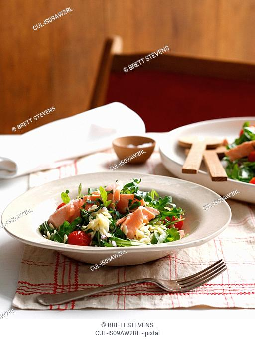 Bowl of poached salmon orzo with cherry tomatoes and rocket