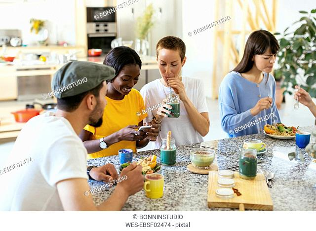 Friends sitting at kitchen counter eating and drinking
