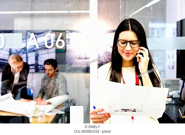 Young woman in office holding paperwork using mobile telephone