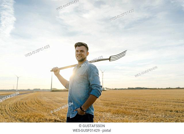 Portrait of smiling young man holding pitchfork standing on stubble field