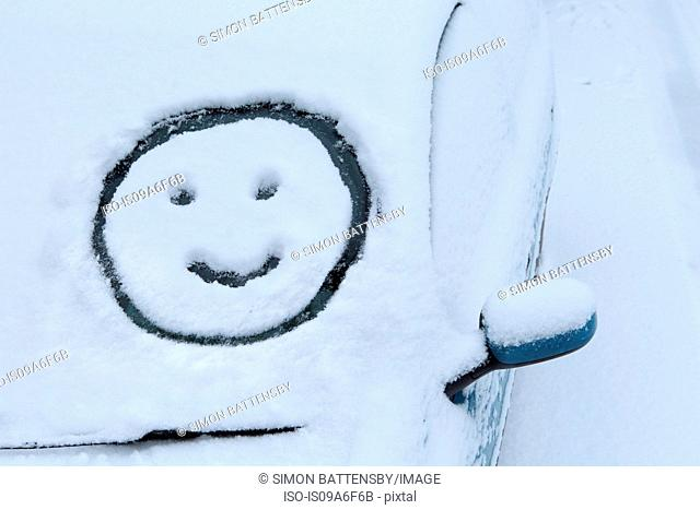 Smiley face drawn in snow on car windscreen