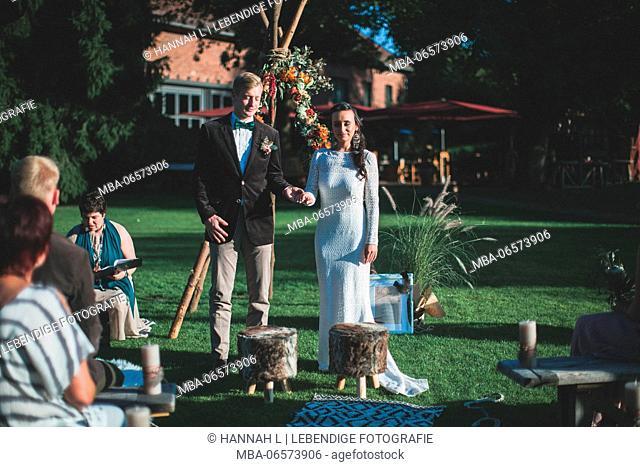 Alternate bridal couple at spiritual wedding ceremony outdoors