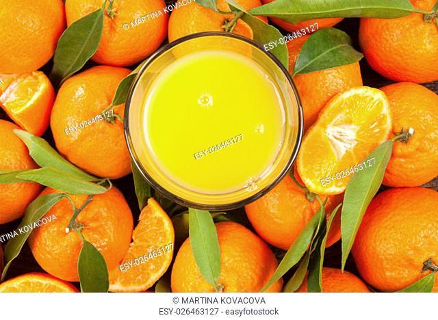 Fresh ripe mandarines with green leaves and orange juice seamless backdrop, flat lay, top view. Organic fresh mandarines, healthy fruit eating
