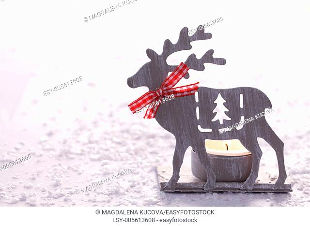 Christmas candlestick on white snowy background