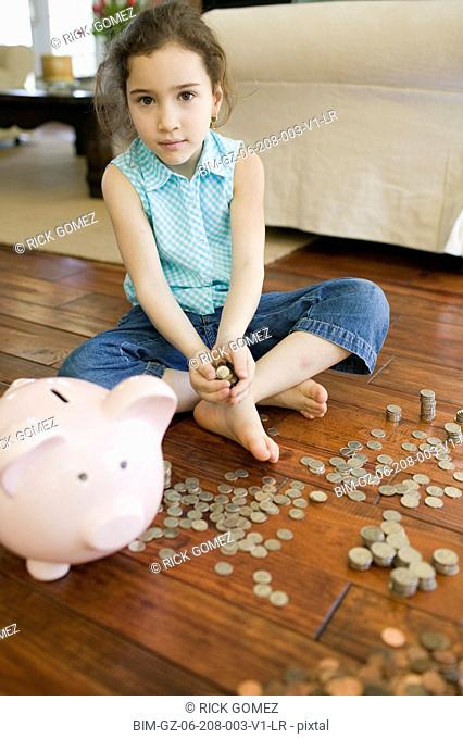 Young girl counting money next to piggy bank