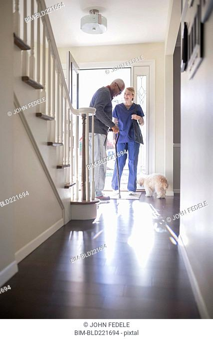 Nurse helping patient walk with cane