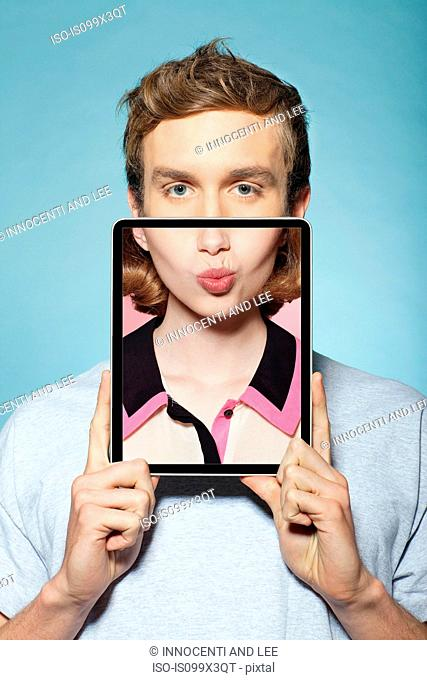Man covering half his face with digital tablet, with womans mouth