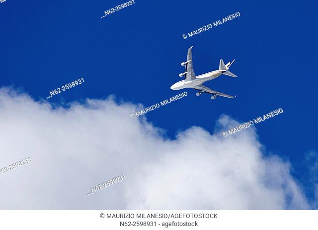 An airplane, airbus, flying in the sky-blue, to the clouds