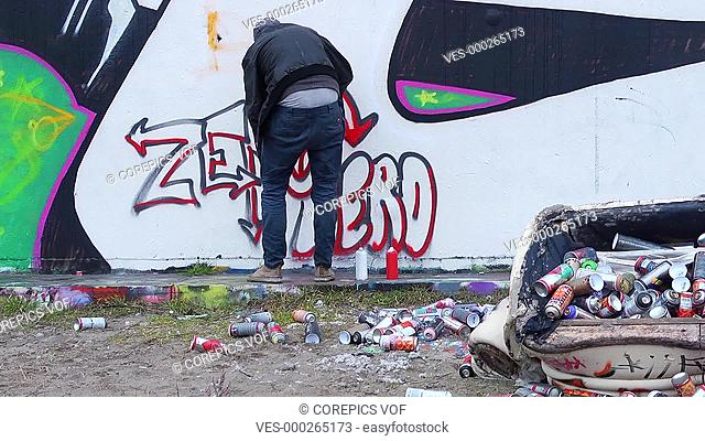 Graffiti artist at work behind an upturned couch, littered with empty spray cans