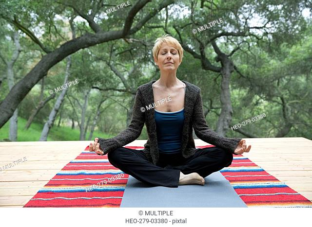 Serene woman meditating in lotus position on deck