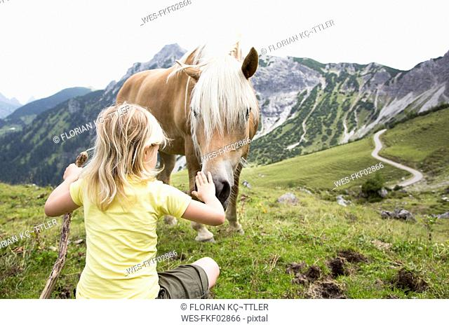 Austria, South Tyrol, young girl with horse on meadow