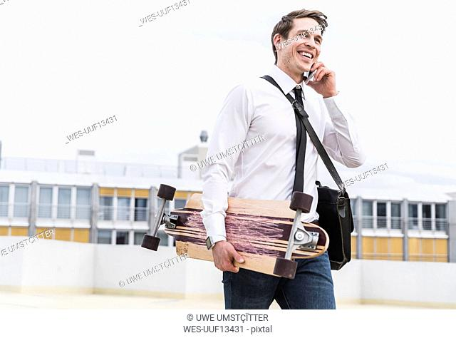 Happy businessman with cell phone and skateboard walking at parking garage