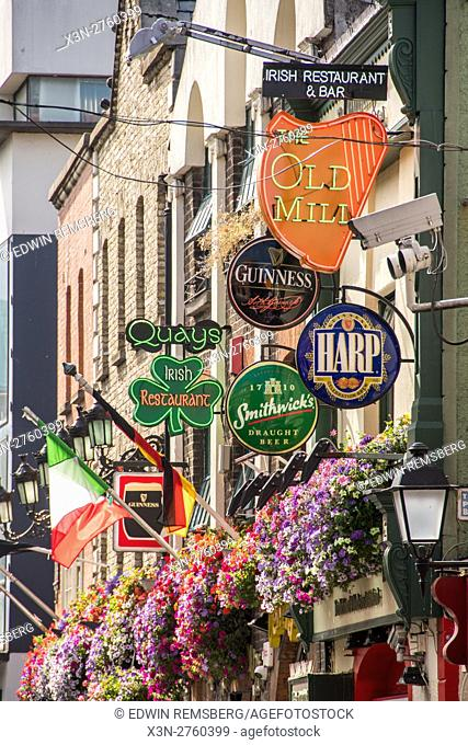 Dublin, Ireland- Colorful neon bar signs and flags outside of a bar in the city of Dublin, the capitol of the Republic of Ireland located on Ireland's eastern...