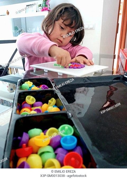 Little girl playing with plastic pieces