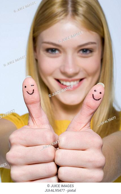Young woman with smiley faces on thumbs