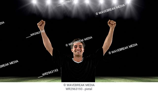Successful soccer player with arms raised at stadium