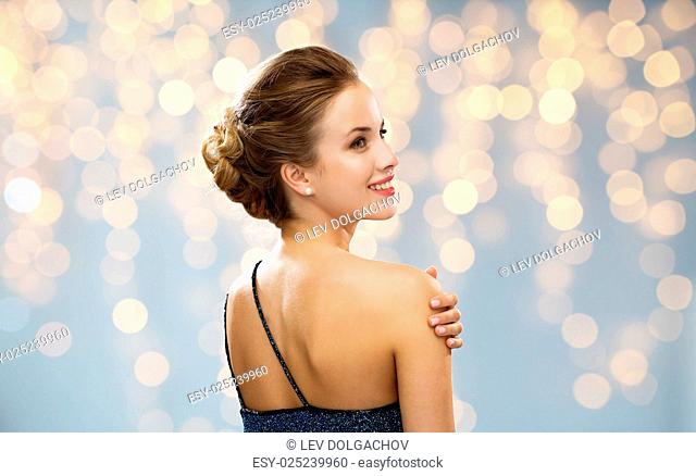 people, holidays and glamour concept - smiling woman in evening dress from the back over lights background