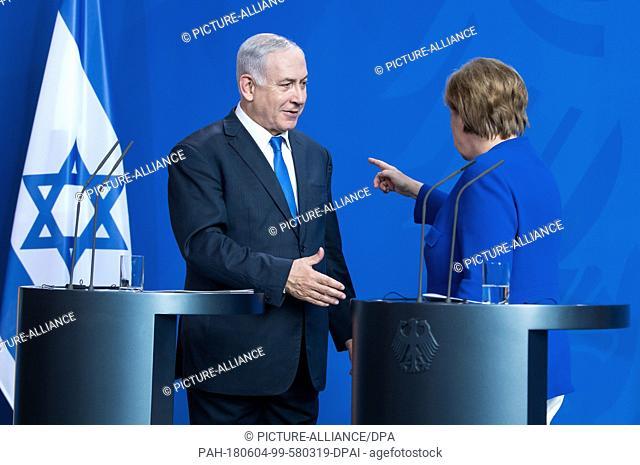 04 June 2018, Germany, Berlin: Benjamin Netanyahu, PMof Israel, attempting to shake hands with German Chancellor Angela Merkel (R
