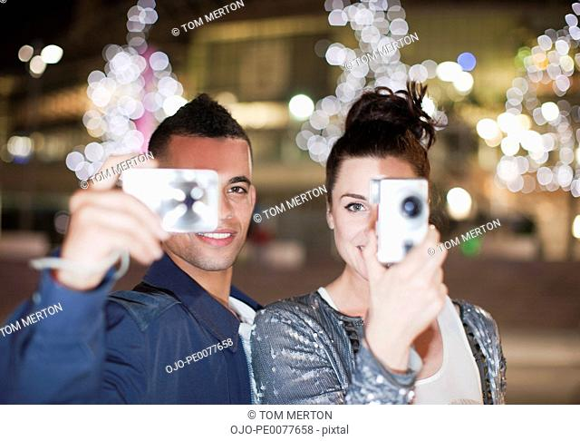 Couple taking pictures on city street at night