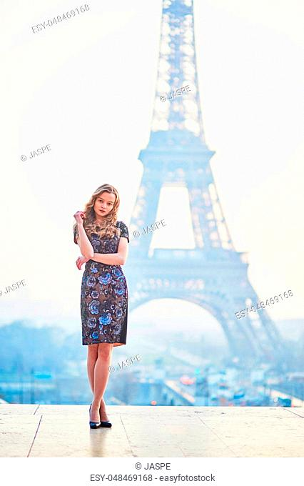 Beautiful elegant Parisian woman near the Eiffel tower at early morning