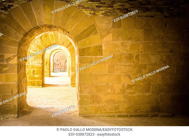 Italy - Old castle of Syracuse in Siciliy. Archs made of stone in perspective