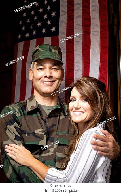 Soldier with wife embracing under american flag