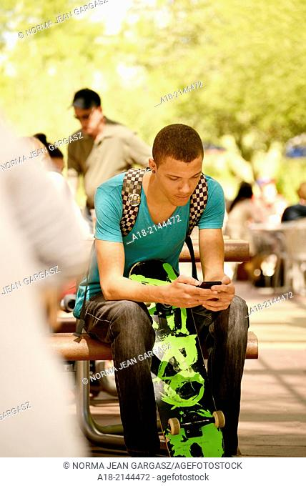 A young man texting on a college campus