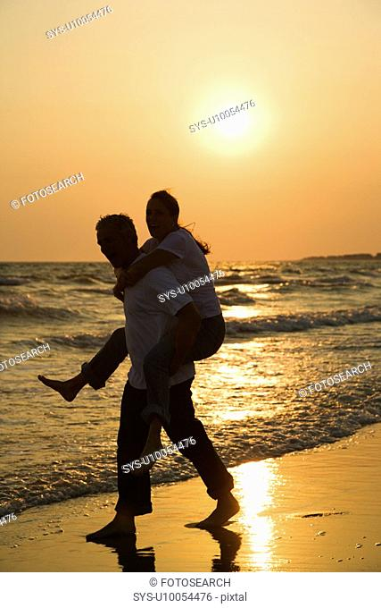 Caucasian mid-adult male carrying female piggyback on beach at sunset