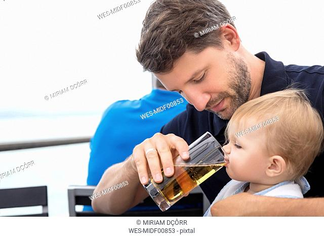 Father giving little daughter something to drink