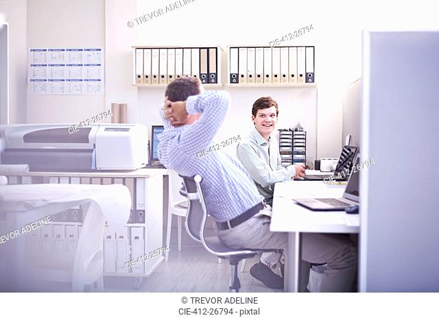Architects talking at desk in office
