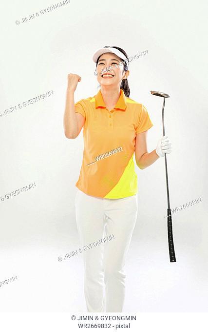 Young smiling Korean female golfer posing